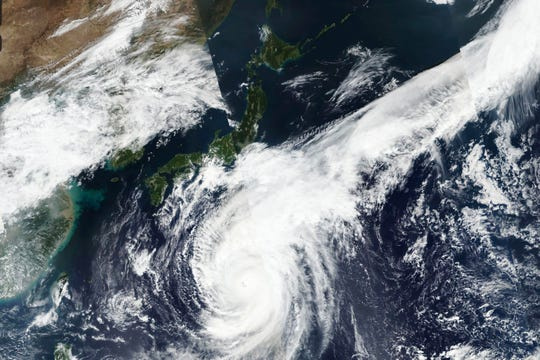 This Oct. 10, 2019, satellite photo taken by NASA-NOAA's Suomi NPP satellite shows typhoon Hagibis approaching Japan, center left.  Japan's weather agency is warning a powerful typhoon may bring torrential rains to central Japan over the weekend. (NASA Worldview, Earth Observing System Data and Information System