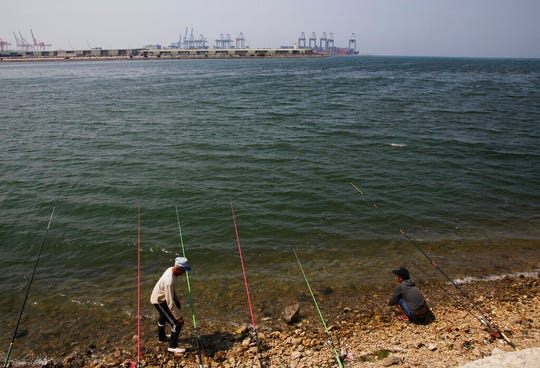 Men fish in front of the Red Sea port city of Jiddah, Saudi Arabia, Friday, Oct. 11, 2019. Iranian officials say two missiles struck an Iranian tanker traveling through the Red Sea off the coast of Saudi Arabia.
