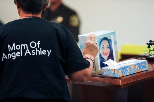 Kristine Young, mother of Ashley Young, gestures to a box containing her daughter's ashes during the sentencing of Jared Chance in Kent County Circuit Court,  Thursday, Oct. 10, 2019, in Grand Rapids, Mich.