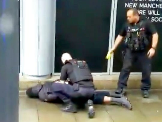 In this image taken from mobile phone footage, police arrest a man outside the Arndale Centre in Manchester, England, Friday October 11, 2019, after a stabbing incident at the shopping center that left four people injured.