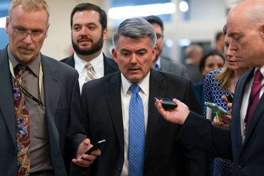 In this March 13, 2019 file photo, reporters pose questions to Sen. Cory Gardner, R-Colo., on his way to a vote at the Capitol in Washington. Twelve times on Thursday, Oct. 10, 2019, Gardner refused to answer whether the president should ask foreign countries to investigate political rivals?