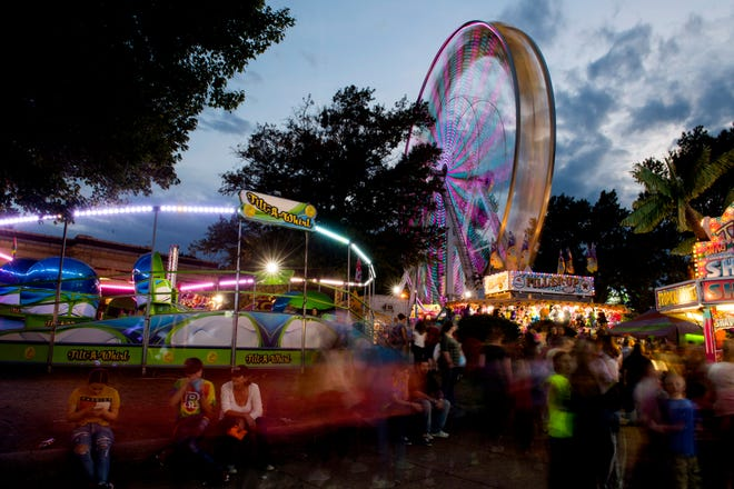 The fair rides create a blur of light and humans during a long exposure on the West Branch Library lawn at the 98th Annual West Side Nut Club Fall Festival Thursday evening.