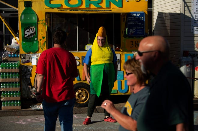 Sam DeVoy hawks corn on the cob while entertaining passersby with a bit of dancing outside the University of Southern Indiana Art Club's Booth 38 at the 98th West Side Nut Club Fall Festival Tuesday evening.