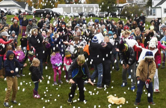 Children look to catch or retrieve pingpong balls for prizes at last year's Fall Festival in Sister Bay. The popular ball drop takes place at 2 p.m. Sunday.