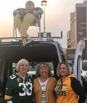 Sisters Debbie Gore, from left, Sue Gutzman and Lori Michaels have been bringing HeBeG.B., up on the roof, to their family tailgate for 30 years.