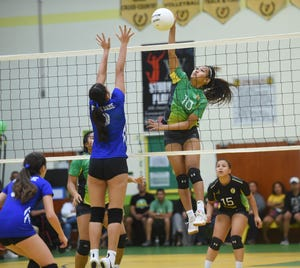 In this file photo from Oct. 11, Kiana Rivera, in green, hits against the Notre Dame Royals in a battle of undefeated teams. Her hitting, blocking, and defense helped JFK to a perfect 11-0 record in the IIAAG High School Girls Volleyball season. Rivera was one of four Islanders named to the All-Island First Team following a recent coaches' vote.