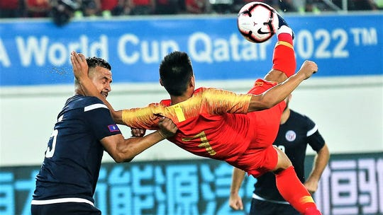 China's Wu Lei, No. 7, attempts a bicycle kick past Guam defender Shawn Nicklaw during the group A match between China and Guam at the FIFA World Cup Qatar 2022 and AFC Asian Cup China 2023 Preliminary Joint Qualification Round 2 in Guangzhou, China on Oct. 10, 2019