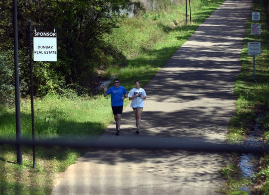 Runners pass by on the Longleaf Trace in Hattiesburg which also allows for biking, walking and horse riding.