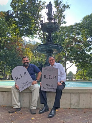 """Abraham Brown, left, director of Hispanic outreach and ministry at Holy Name of Jesus Catholic Church, and Henderson County Judge-executive Brad Schneider show off a couple of the """"tombstones"""" that will be available in a """"graveyard"""" that will be set up for a celebration of the Mexican Dia de Los Muertos (Day of the Dead) holiday in Henderson's Central Park on Saturday, Nov. 2. Much as many Americans will remember their dearly departed on All Saints' Day on Nov 1, many Mexicans visit the graves of their late loved ones to picnic and take favorite treats to those who have passed."""