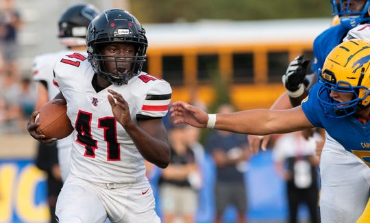 """North Central High School junior Monioluwa """"Jerry"""" Asekunowo (41) rushes the ball out of the backfield during the first half of an IHSAA high school football game at Carmel High School, Friday, Sept. 27, 2019."""