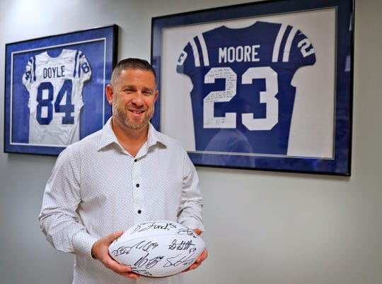Signed jerseys of Colts tight end Jack Doyle, left, and cornerback Kenny Moore II hang in sports agent Buddy Baker's offices, Friday, Oct. 11, 2019.  Baker holds an ball autographed by clients on a trip to the Dominican Republic.  Baker is President and CEO of Exclusive Sports Group, LLC.