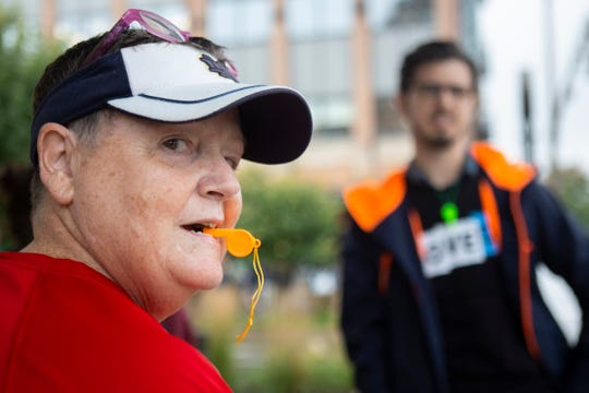 """Peggy Appleby, of South Bend, blows a whistle before the """"Whistles for Whistleblowers"""" demonstration at the corner of Eddy St. and Angela Blvd in South Bend, on Friday, Oct. 11, 2019. This is to protest a talk on campus by U.S. Attorney General William Barr. in a nod to the whistleblower complaint that has led to a U.S. House inquiry of whether to impeach President Donald Trump."""
