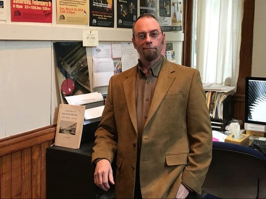 Mark Costa stands before a wall of the Trumansburg Conservatory of Fine Arts' many concert posters.  He has brought a new life to the 168-year-old facility.