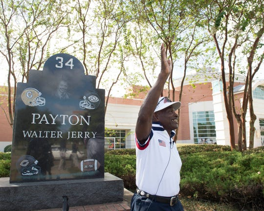 Former NFL player and Jackson State University golf coach Eddie Payton, in front of the  Walter Payton Recreation and Wellness Center in Jackson, Miss., waves to alumni during the start of homecoming weekend on Friday, Oct. 11, 2019. Payton is the older brother of the late NFL Hall of Fame inductee Walter Payton, who also played football at JSU.