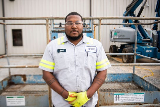 Veteran Bradford Bady stands in front of equipment he services at United Rentals in Jackson, Tenn. where he recently started a new career as an equipment service technician with the help of nonprofit Workforce Opportunity Services.