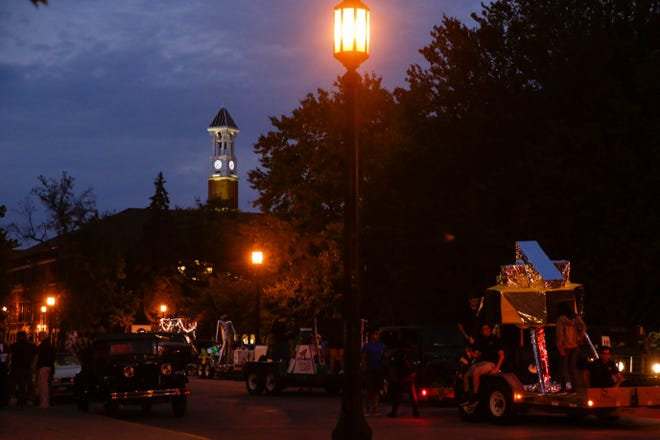 The Purdue clock tower is illuminated above the start of the 2019 Purdue Homecoming Parade, Thursday, Oct. 10, 2019 in West Lafayette.