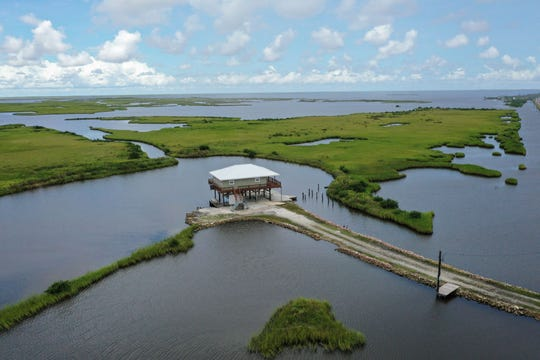 GRAND ISLE, LA - AUGUST 24: A home on stilts sits amidst coastal waters and marshlands along Louisiana Highway 1 on August 24, 2019 in Grand Isle, Louisiana.