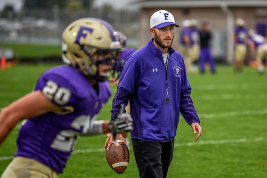 Fowlerville's head coach Jon Fletcher, right, looks on during pre-game drills before the Gladiators game against St. Johns on Friday, Oct. 11, 2019, at Fowlerville High School.