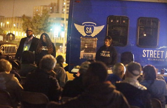 Occupants of the Tent City homeless encampment in downtown Milwaukee listen to members of the Milwaukee Street Angels at a town hall meeting at the encampment Thursday evening.