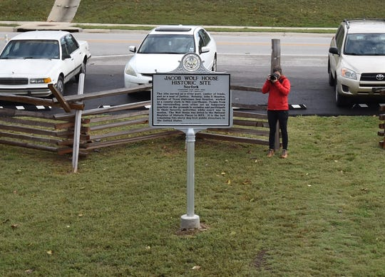 A tourist snaps a photo of the new historical marker on display at the Jacob Wolf House Historic Site in Norfork on Friday.