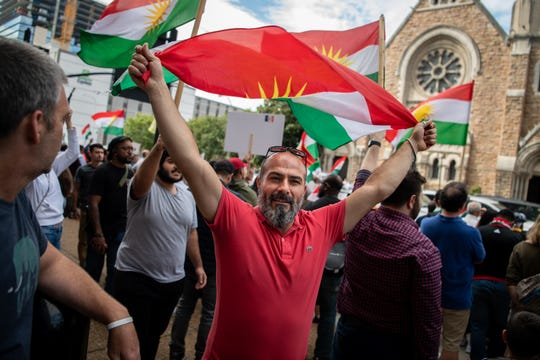 Sakir Cinar, of Nashville, waves a Kurdish flag during a rally against the withdrawal of troops from Syria outside of the Estes Kefauver Federal Building in Nashville, Tenn., Friday, Oct. 11, 2019.