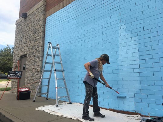 Local artist April James works on Brentwood's first public mural in the CityPark development.