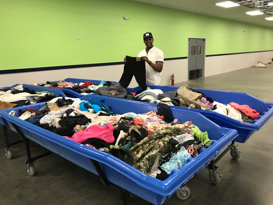 Reginald Green, who will manage the new Goodwill Outlet, shows off four merchandise-filled rolling tables that will be replenished to provide a continuously changing assortment every day in the outlet.