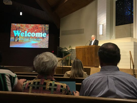 Bill Watkins, the pulpit minister at Crieve Hall Church of Christ, welcomes church members and guests to a community prayer event.