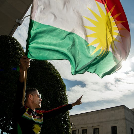 Zee Ali, of Nashville, waves a Kurdish flag during a rally against the withdrawal of troops from Syria outside of the Estes Kefauver Federal Building in Nashville, Tenn., Friday, Oct. 11, 2019.