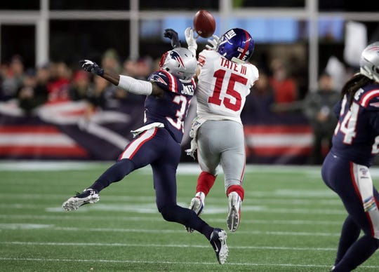 New York Giants wide receiver Golden Tate, right, catches a touchdown pass under pressure from New England Patriots defensive back Jonathan Jones in the first half of an NFL football game, Thursday, Oct. 10, 2019, in Foxborough, Mass.