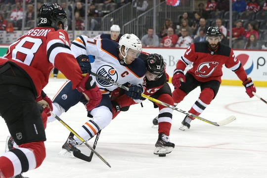 Oct 10, 2019; Newark, NJ, USA; Edmonton Oilers center Connor McDavid (97) battles New Jersey Devils center Nico Hischier (13) for the puck during the first period at Prudential Center.