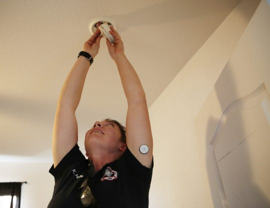 Las Cruces firefighter Kristin Wahlen installs a new smoke alarm in the home of a Domino's Pizza customer, Thursday, Oct. 10, 2019.