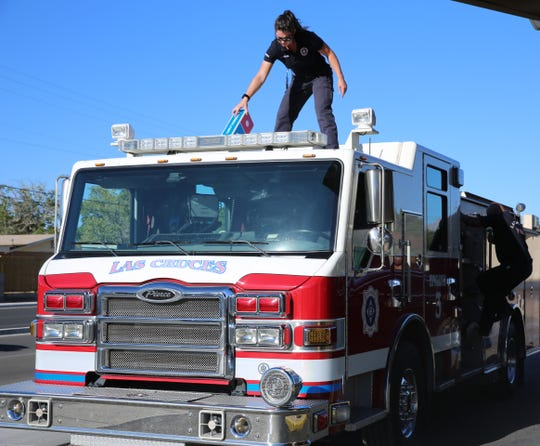 Las Cruces Firefighter Kristin Wahlen afixes a Domino's Pizza car-topper to Engine 3, Thursday Oct. 10, 2019.