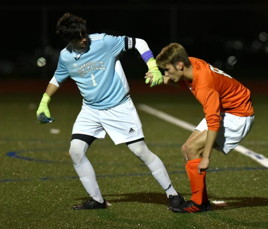 Mustang goalie Robert Damron, left, gives a hand off the turf to teammate Jacob Pichler at the end of the first half.
