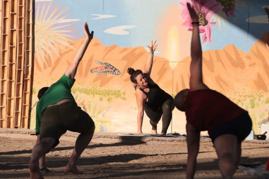 People participate in a yoga class at the Joshua Tree Music Festival in Joshua Tree, Calif., on Thursday, October 10, 2019.