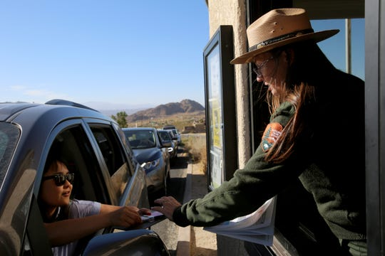 Joshua Tree National Park visitor use assistant Cynthia Libby receives payment from first-time visitor Juyeon Lee of Los Angeles on Thursday, Oct. 10, 2019. Lee brought along six other family members who were visiting California from South Korea.
