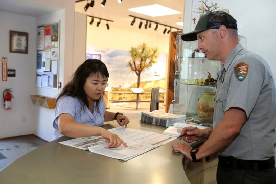 Joshua Tree National Park interpretive ranger Christian Delich, right, gives first-time visitor Juyeon Lee of Los Angeles a park map inside the Visitors Center in Joshua Tree, Calif., on Thursday, October 10, 2019. Visitors can also purchase day use passes at the Visitors Center. Delich recommends checking the park's website prior to a visit, which is updated everyday.