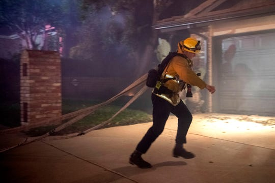 A firefighter runs up a driveway with hoses as the Saddleridge fire threatens homes in Granada Hills, Calif., Friday, Oct. 11, 2019.