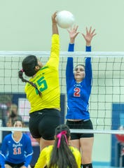 Cheyenne Sandoval hits the ball as Indio's Ariana Flores goes up for the block on Thursday.
