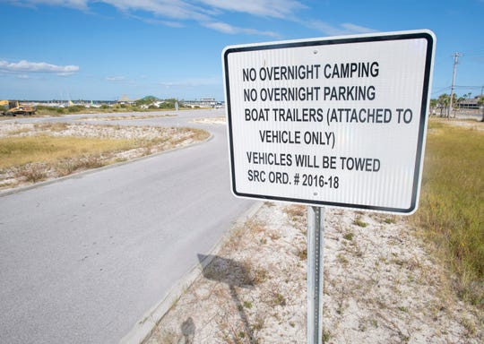 A sign notes there is no overnight camping nor parking at the Sound Side Park parking lot in Navarre Beach.