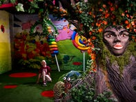 "Zander Hemphill, 11, looks up at the candy cricket sculpture in the ""Wonderland"" room at Candytopia in Scottsdale on Thursday, Oct. 10, 2019. The face on the tree is that of Jackie Sorkin, the curator of the pop-up exhibit."