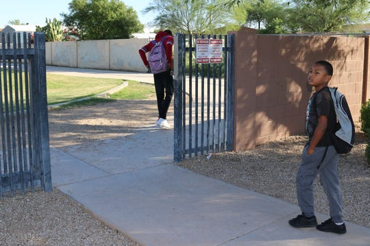 MJ Jones walks through the back gate of Surprise Elementary School on Friday, Oct. 11. Their HOA may soon block this gate.