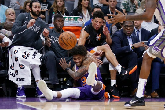 Phoenix Suns forward Kelly Oubre Jr., center, crashes into the Suns bench as he goes for the ball during the second half of the team's NBA preseason basketball game against the Sacramento Kings in Sacramento, Calif., Thursday, Oct. 10, 2019. (AP Photo/Rich Pedroncelli)