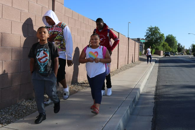 Tyjohn Jones, 17, (back left) walks his siblings MJ, Tyjohnae and Edward to Surprise Elementary School on Friday, Oct. 11.
