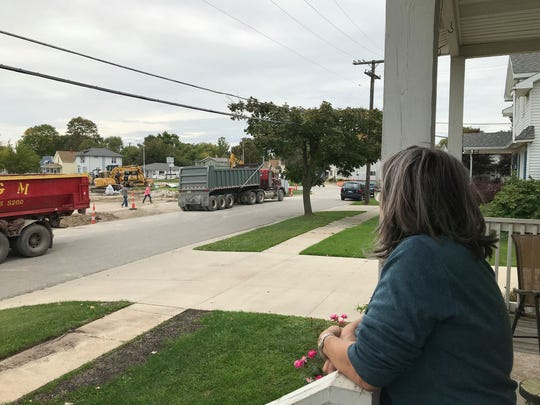 Valerie Hoste watches from her porch as a construction crew works on the site for a new Dollar General at 1251 Water St. in Port Huron on Oct. 11, 2019.