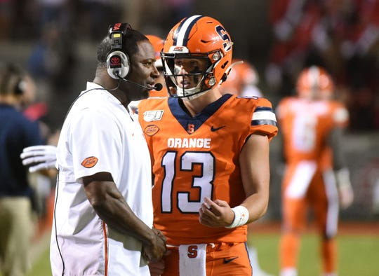 Syracuse Orange head coach Dino Babers (left) talks to quarterback Tommy DeVito (13) during the second half against the North Carolina State Wolfpack at Carter-Finley Stadium. The Wolfpack won 16-10.