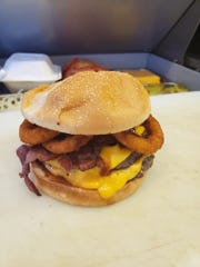 A bacon cheeseburger with onion rings at Dude's Drive Inn.