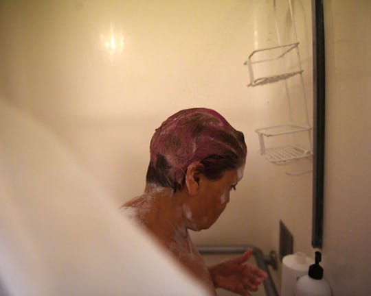 Maria Morales soaps up in the shower at Dorothy's Place. Oct. 11, 2019.