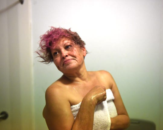 Maria Morales shakes her hair out and dries off after a shower at Dorothy's Place. Oct. 11, 2019.