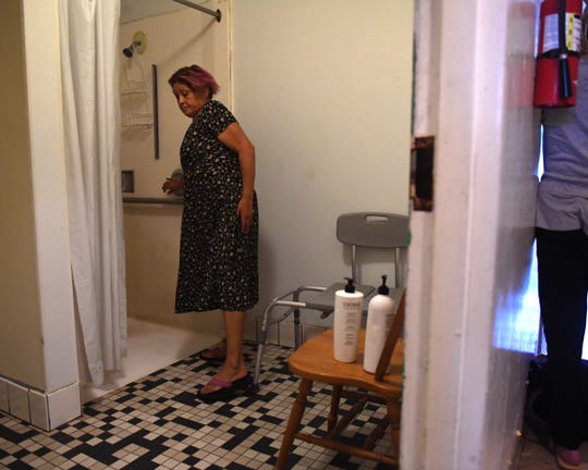 Maria Morales prepares to take a shower at Dorothy's Place. Oct. 11, 2019.